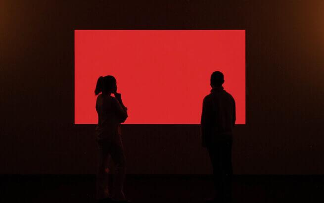 Silueta de dos personas viendo la Instalación de color Rojo llamada Cherry del artista James Turrell en la Exposición del Museo Picasso Málaga 2021